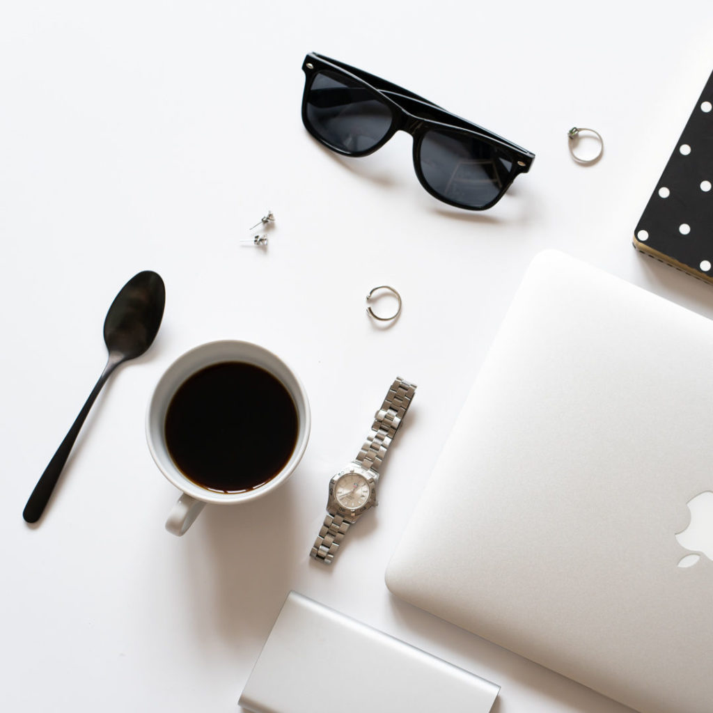 Flatlay smacbookem, brýlemi, kávou ahodinkami