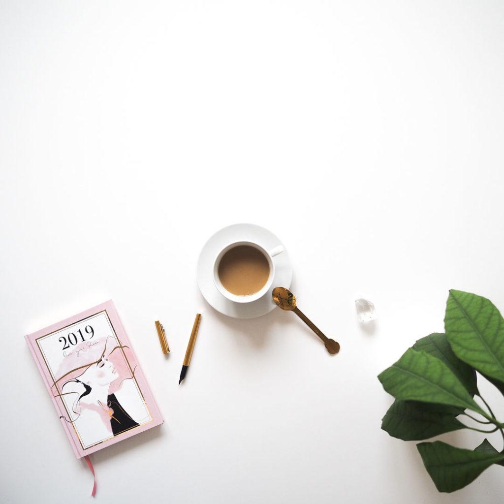 Flatlay záběr sdiářem, kávou, zlatým perem aavokádem vkvětináči