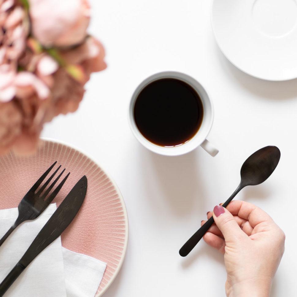 Flatlay s kávou, růžovým talířkem a černými příbory
