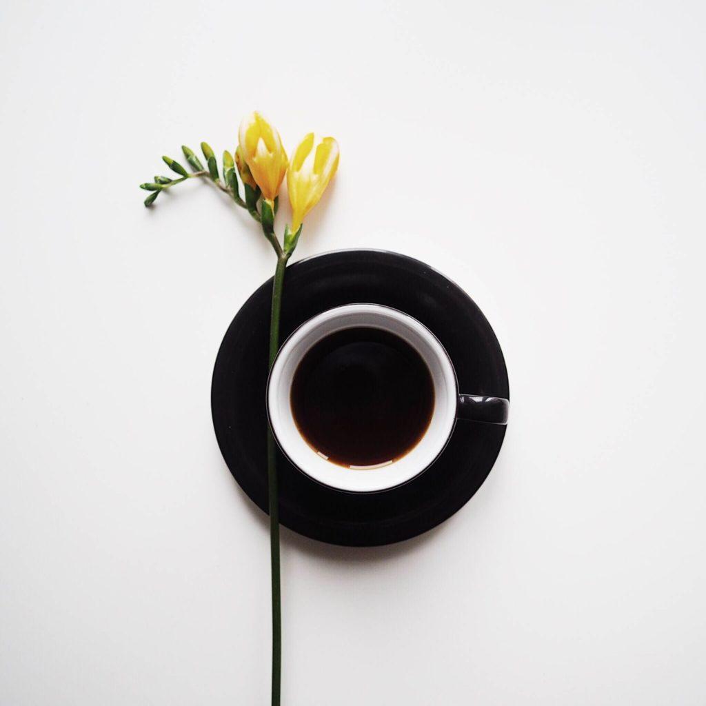 flatlay sčerným šálkem ažlutou květinou