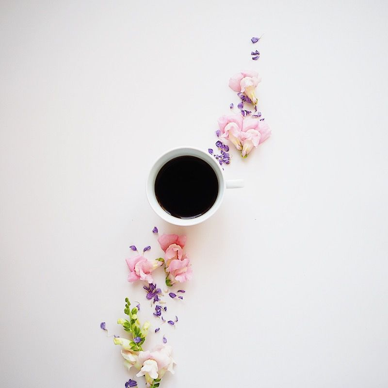 Flatlay with cup of black coffee, pink and violet flowers on awtite backdrop