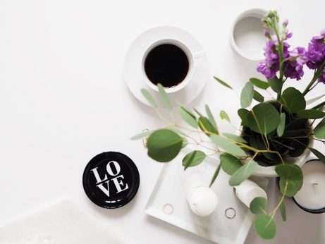 Flatlay with coffee, violet flowers and little black LOVE plate