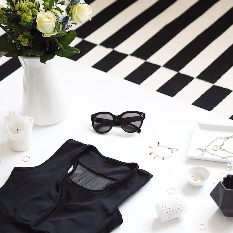Flatlay with cream roses, white backdrop and black top by Mania Fitness Wear