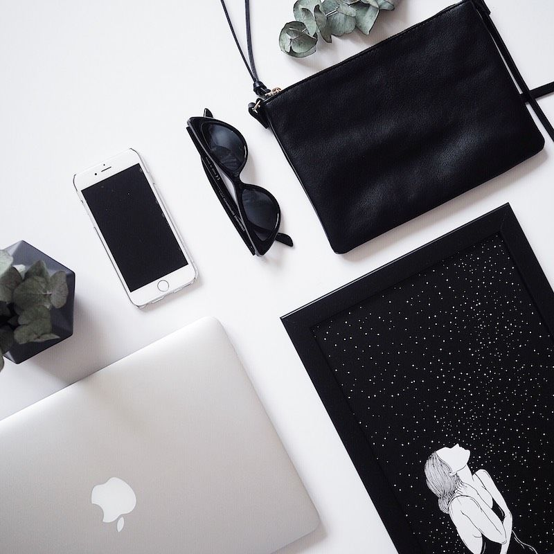 Neatly organized flatlay with macbook, iphone, cross body bag and picture with stars