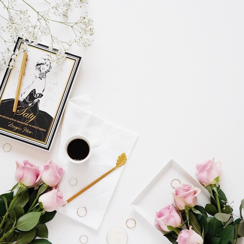 Flatlay with pink roses, coffee and book Dress by Megan Hess on white backdrop