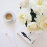 Flatlay fotka s bílými pivoňkami, kávou a knížkou How to be Parisian