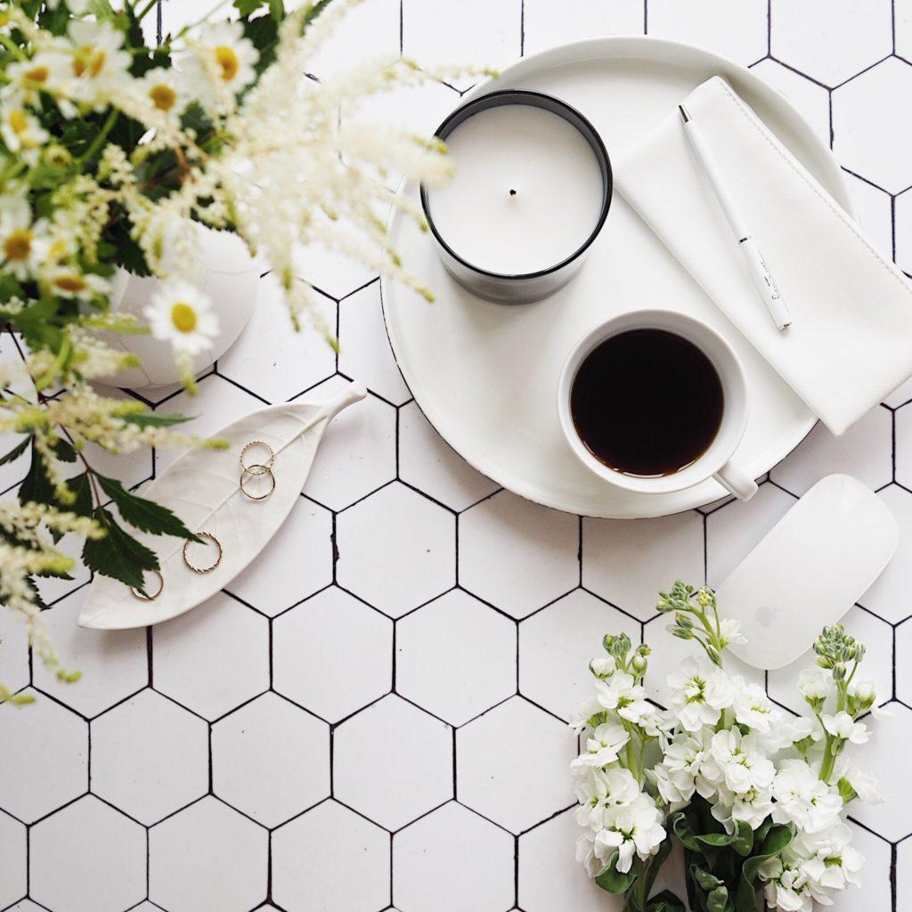 Fotka focená shora, nakachličkovém pozadí je bílý talíř, šálek skávou asvíčka akvětiny sbílými květy