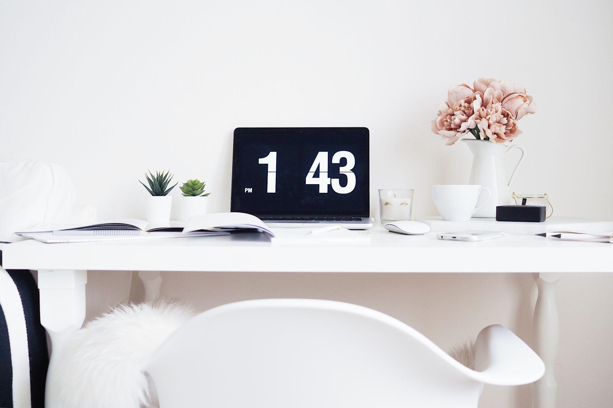 bílý pracovní stůl s otevřeným notebookem, dvěma sukulenty a květinou v bílém džbánku