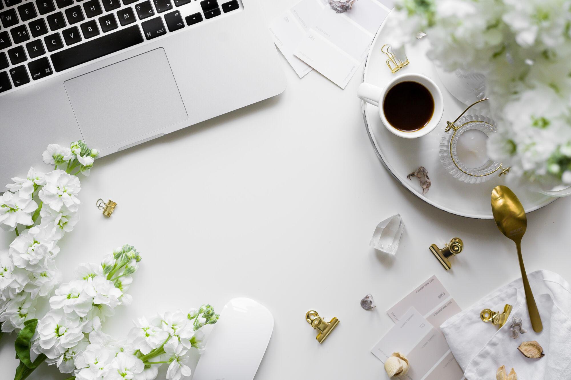 flatlay slaptopem, kávou abílými matiolami
